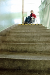 lady-in-wheelchair-at-top-of-stairs-unable-to-exit-building